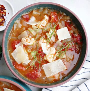 bowl of fennel stew with shrimp in a soup bowl with toppings