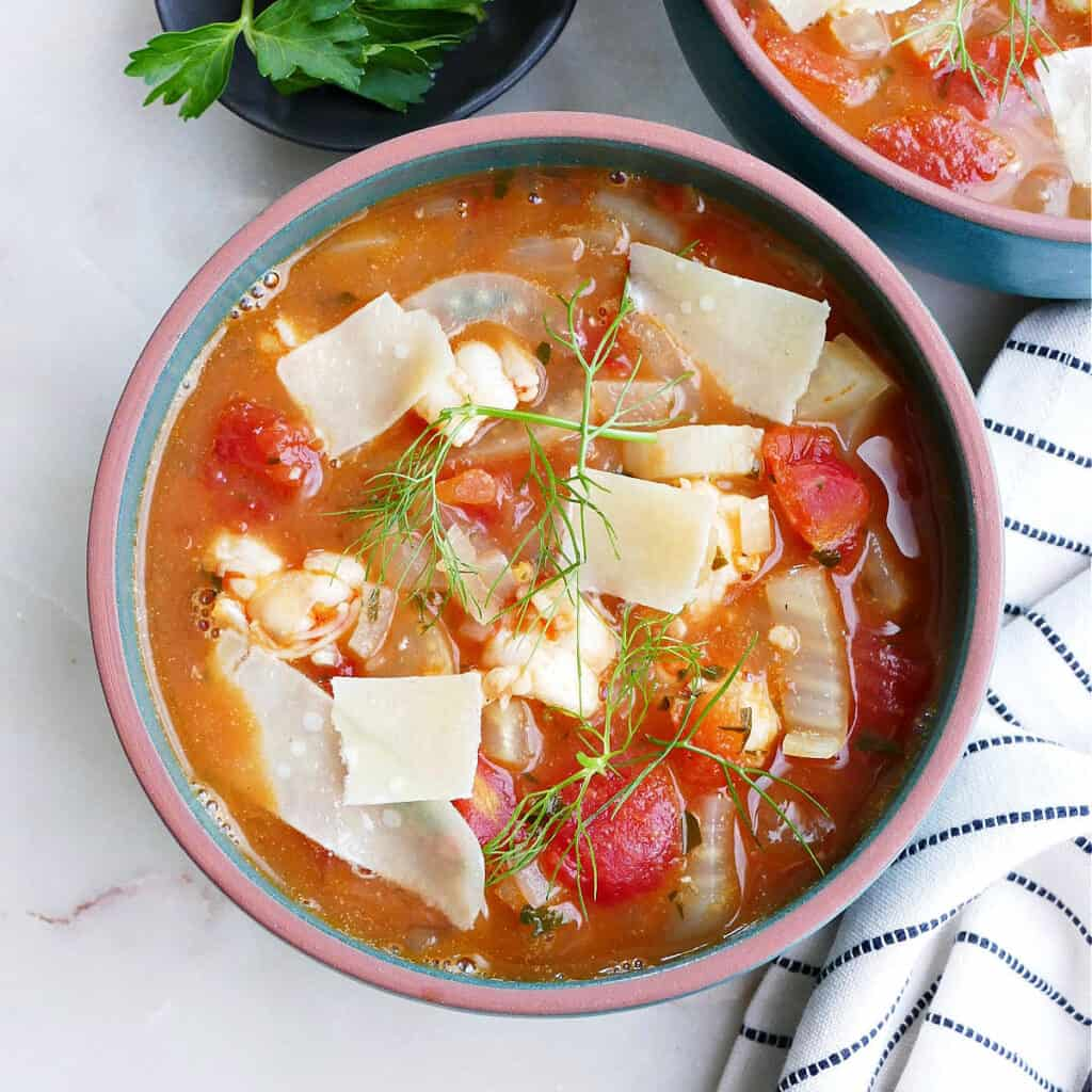 square image of bowl of fennel stew with shrimp in a soup bowl with toppings