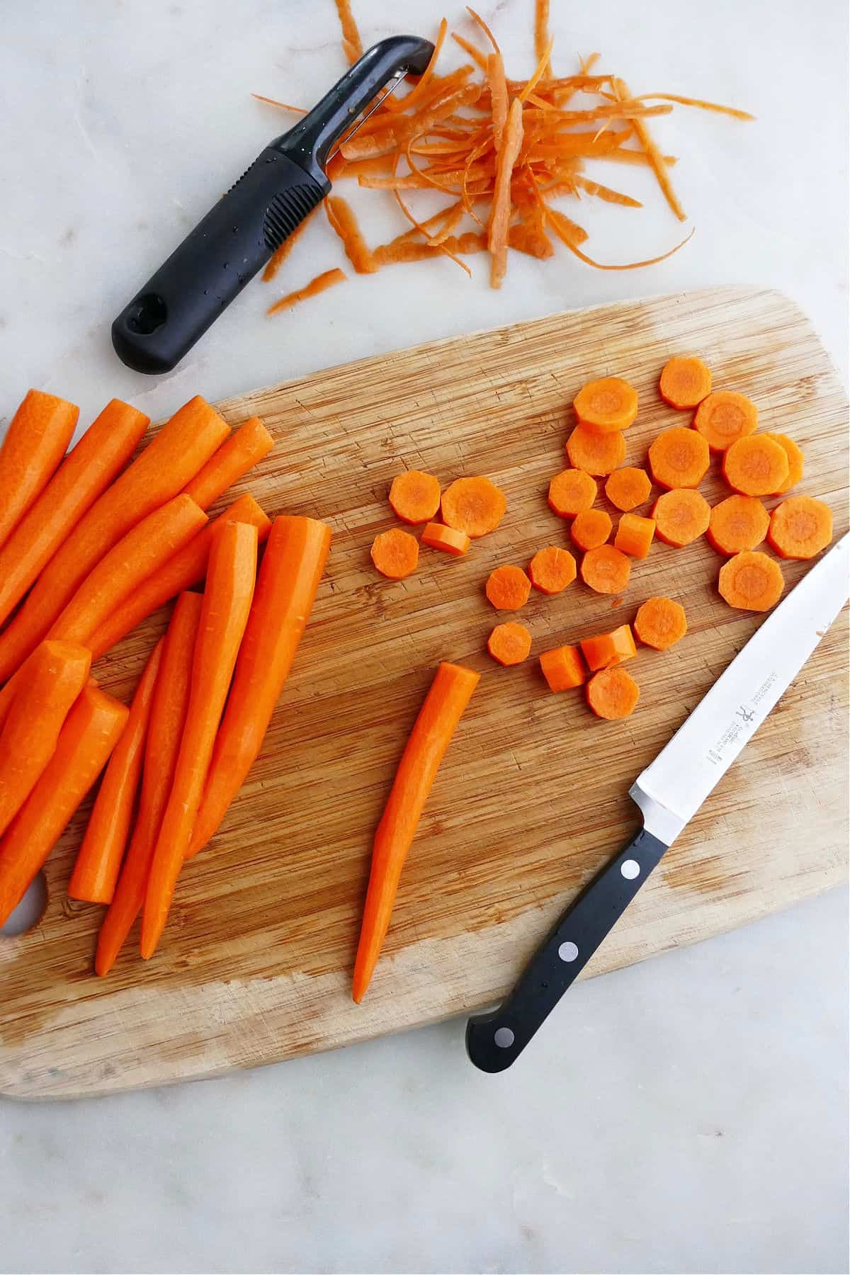 peeled carrots on a cutting board next to carrot slices and peelings
