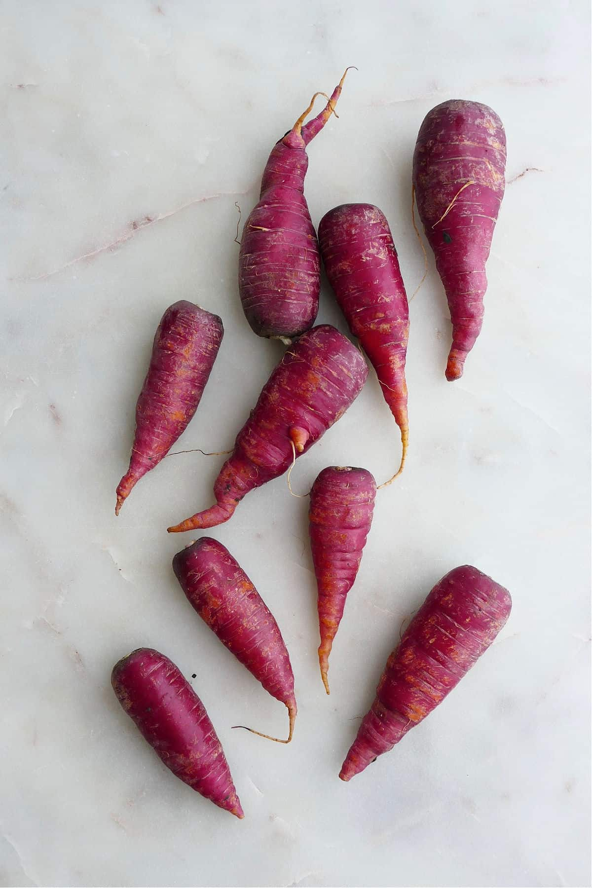 nine cosmic purple carrots spread out next to each other on a white counter