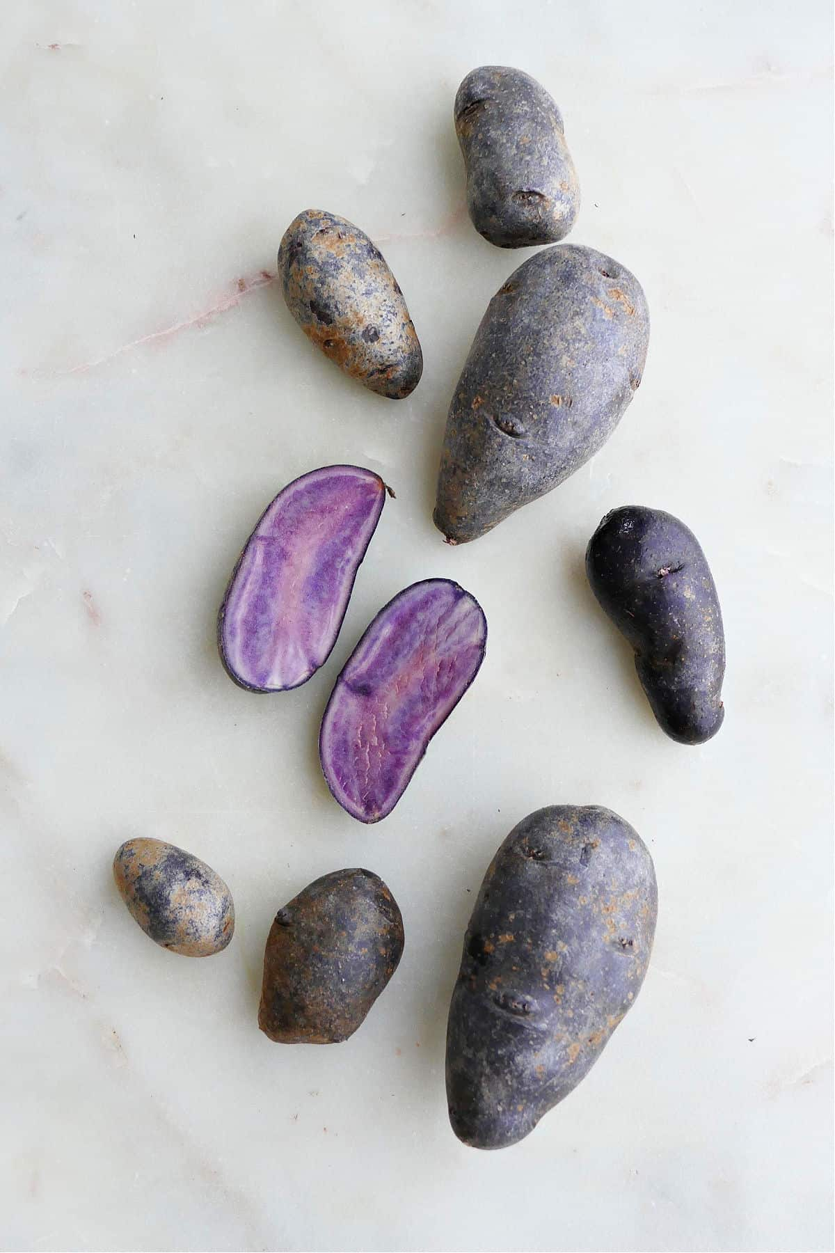 purple potatoes spread out next to each other on a counter