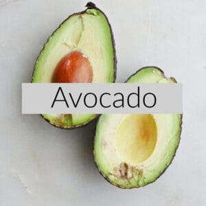 image of a sliced avocado with cut sides up on a counter under the text Avocado