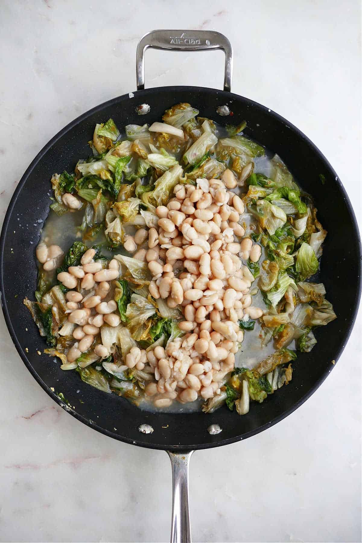 escarole and white beans cooking in a large black skillet on a white counter