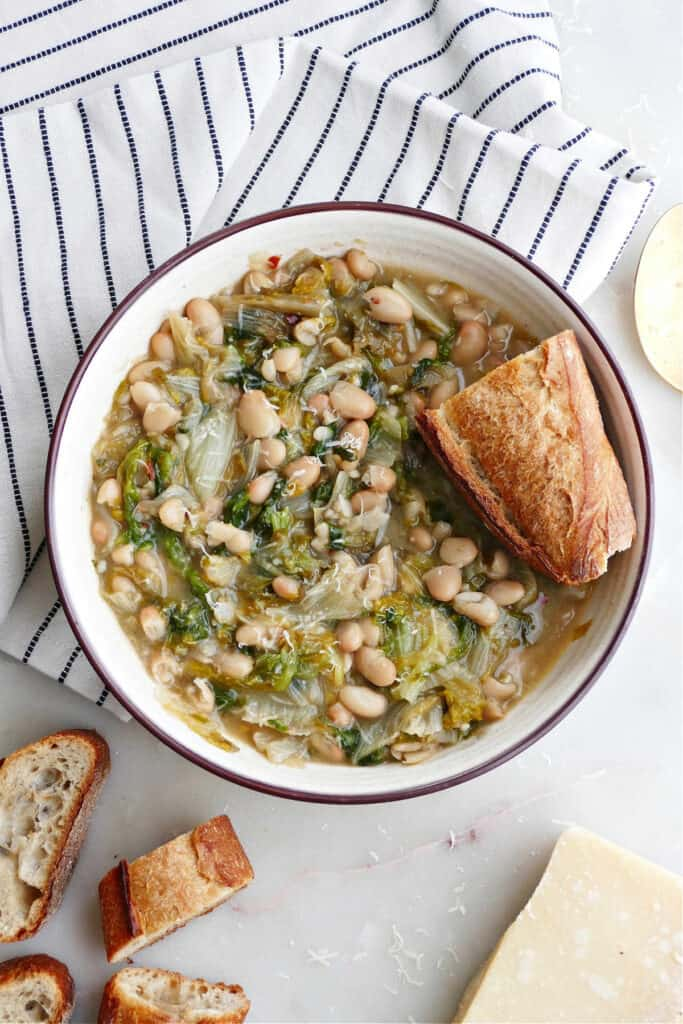 bowl of beans and escarole with bread on a napkin next to ingredients