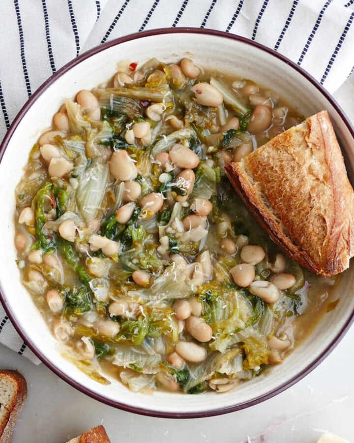 square image of a serving bowl with white beans and escarole and crunchy bread
