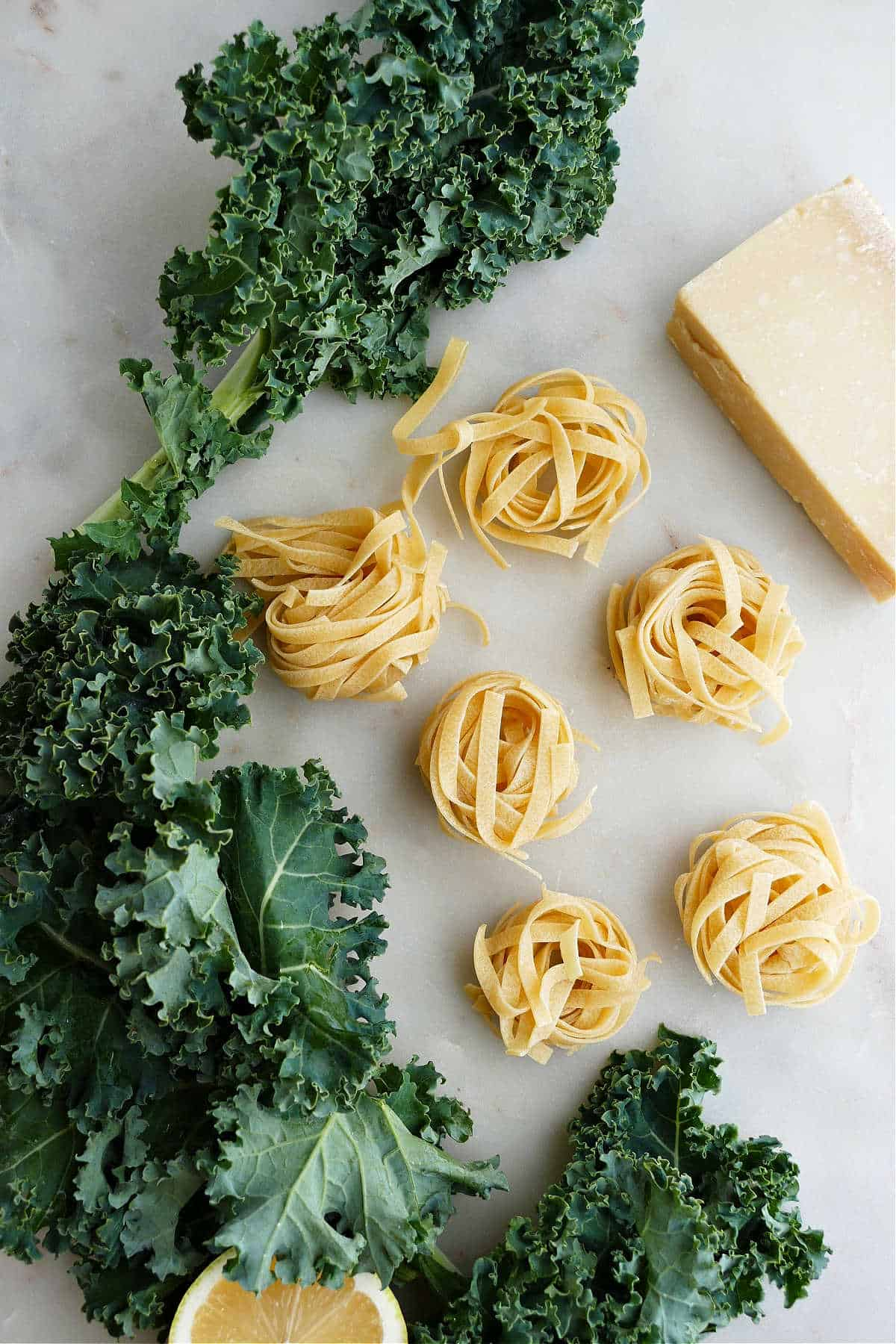 kale leaves, nests of tagliatelle, parmesan, and lemon spread out on a counter
