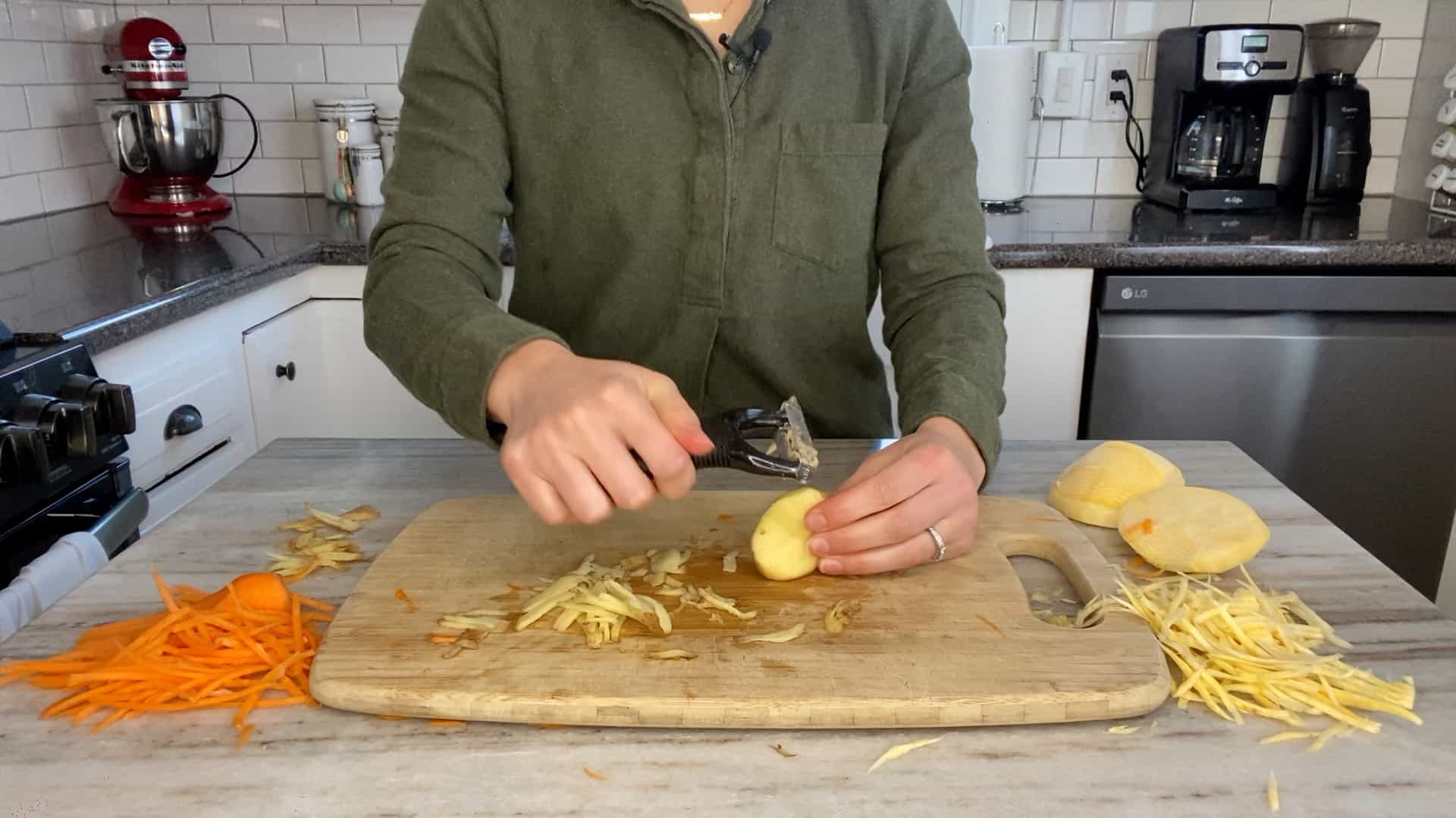 woman slicing a potato with a julienne peeler on a bamboo cutting board