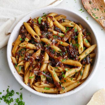 caramelized shallot pasta in a serving bowl next to ingredients on a counter