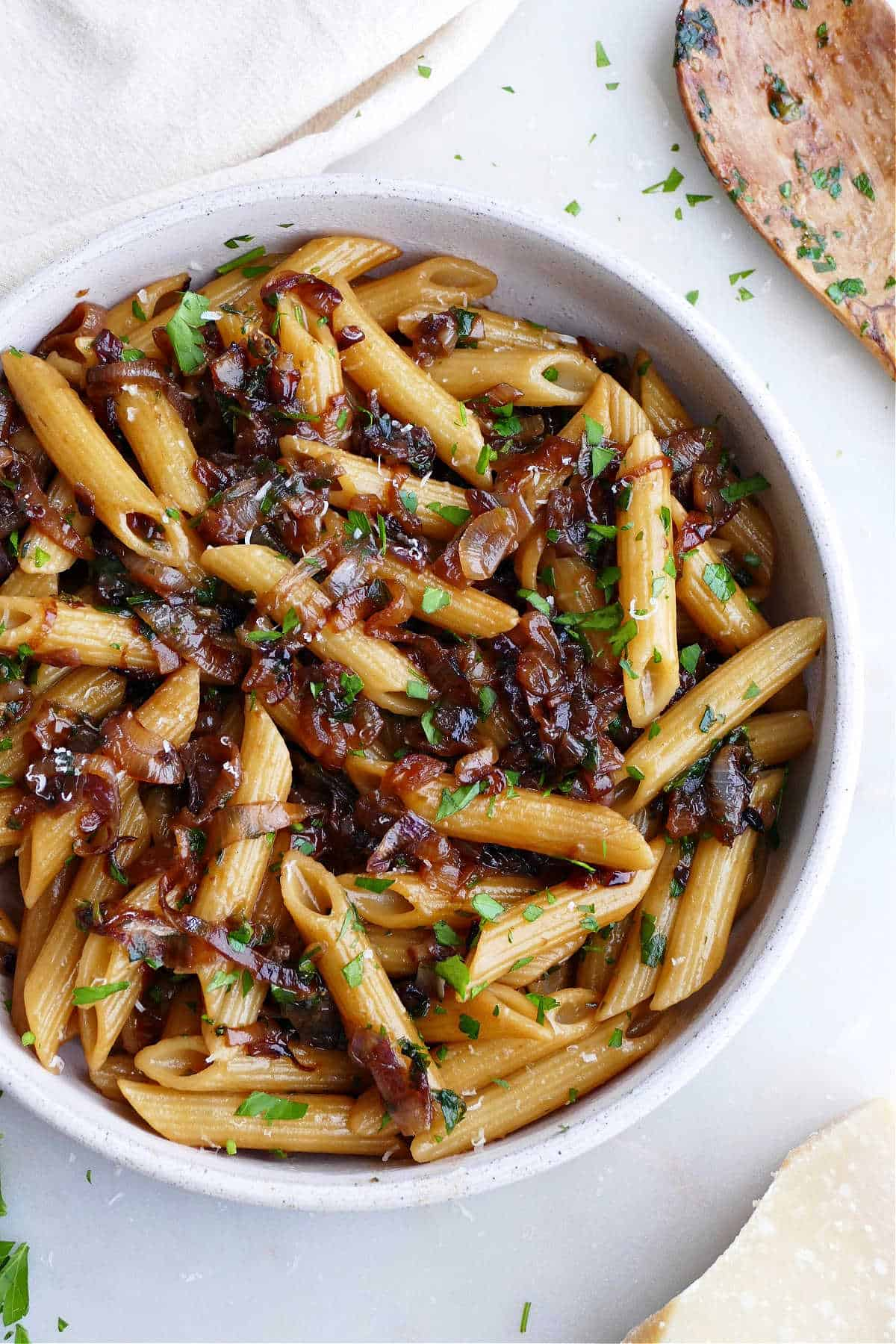 close image of caramelized shallot pasta in a serving bowl topped with parsley