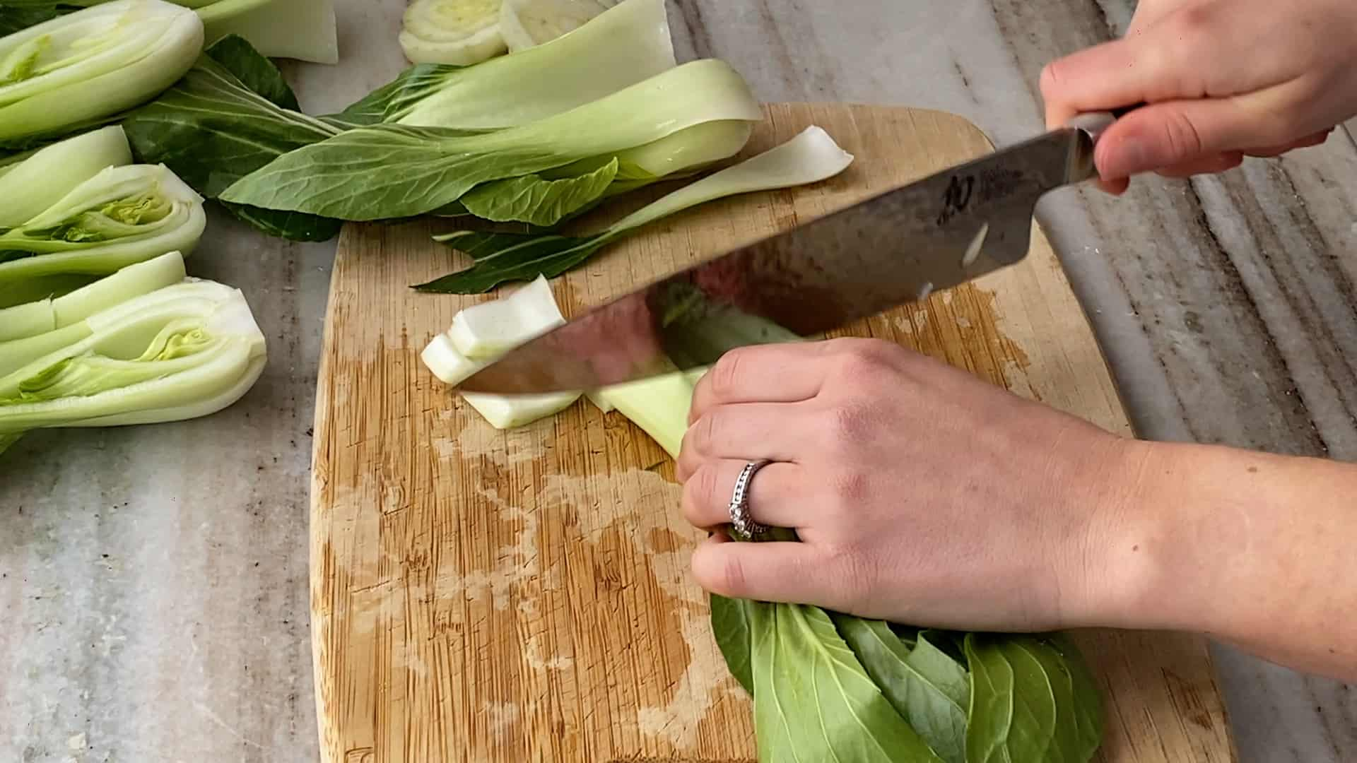 woman chopping bok choy on a bamboo cutting board
