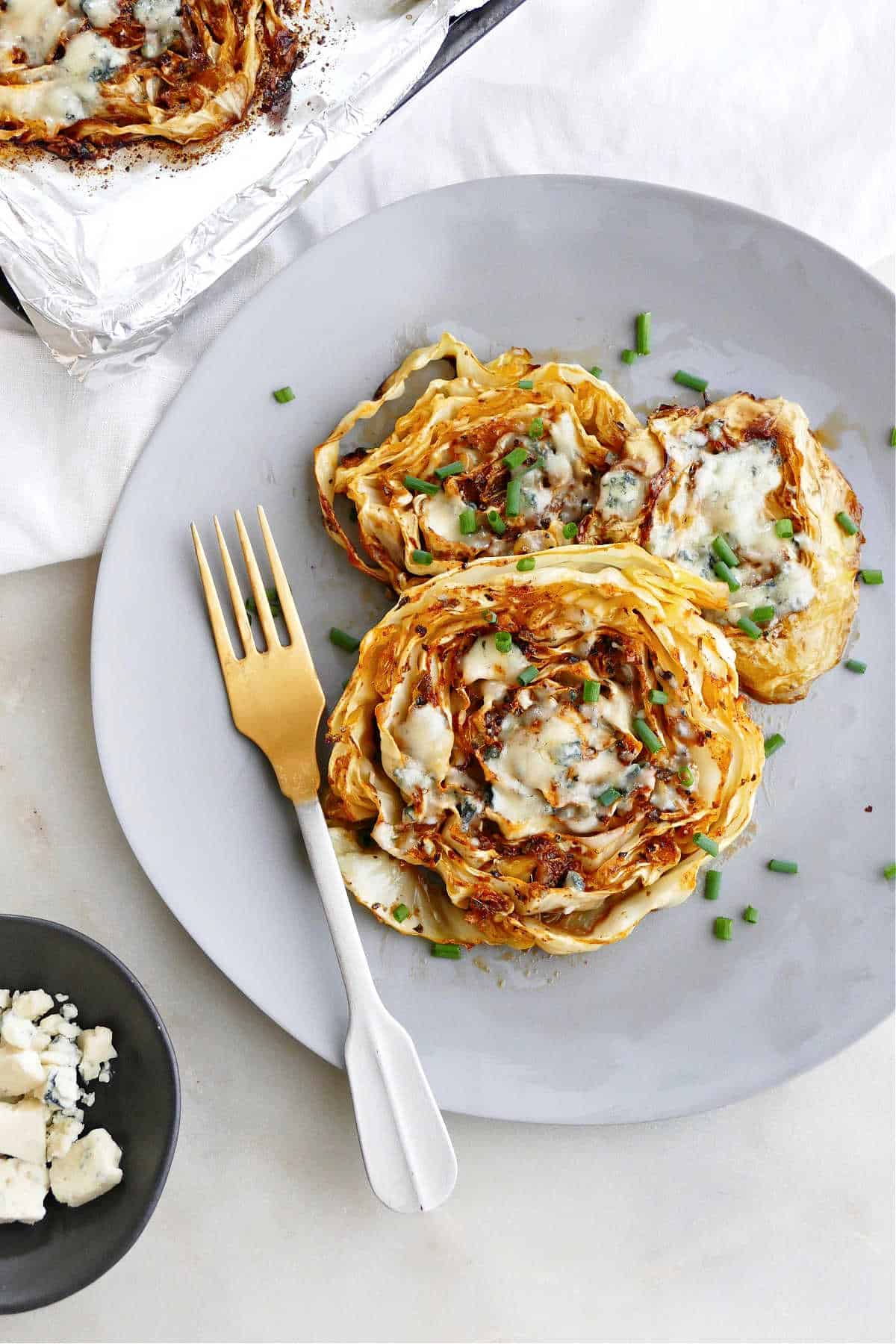 three roasted cabbage steaks on a serving plate with a fork and sliced chives