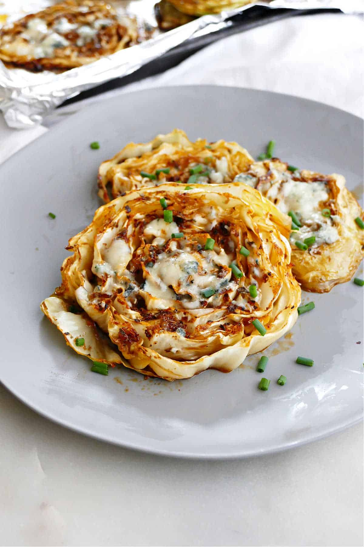 side view of roasted cabbage steaks topped with chives on a serving plate