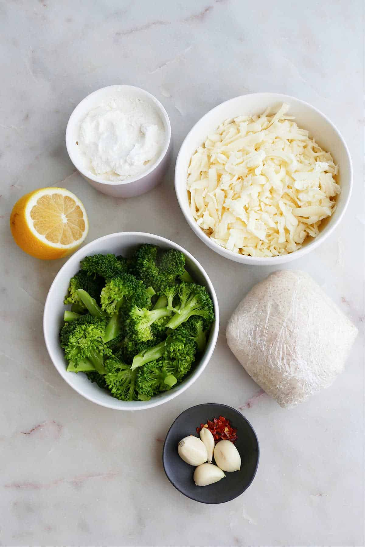 ricotta cheese, mozzarella, broccoli, pizza dough, lemon, garlic, and red pepper flakes on a counter