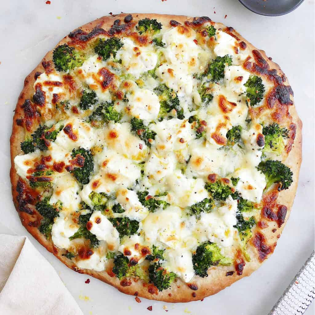 square image of white pizza with broccoli on a counter