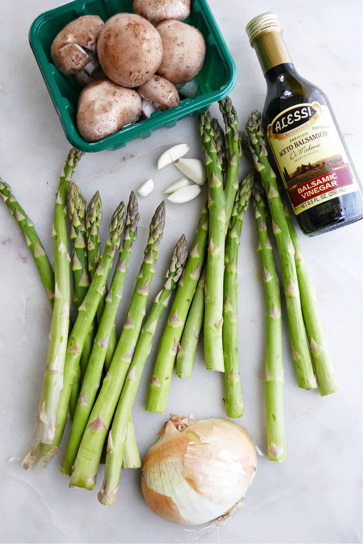 mushrooms, asparagus, garlic, balsamic vinegar, and onion spread out on a counter
