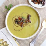 asparagus soup topped with balsamic mushrooms on a placemat on a counter