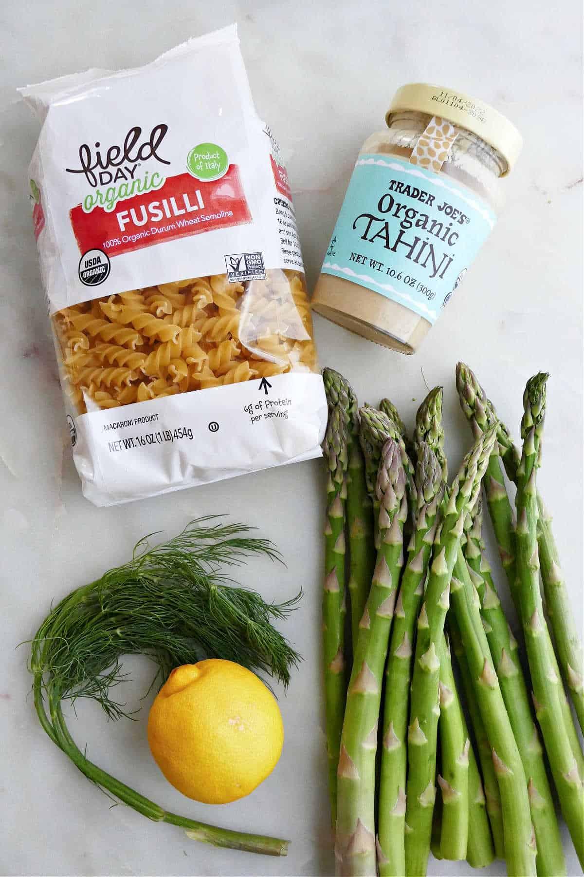 bag of fusilli pasta next to tahini jar, dill, lemon, and asparagus