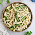 asparagus pasta salad in a bowl next to herbs and toppings on a counter