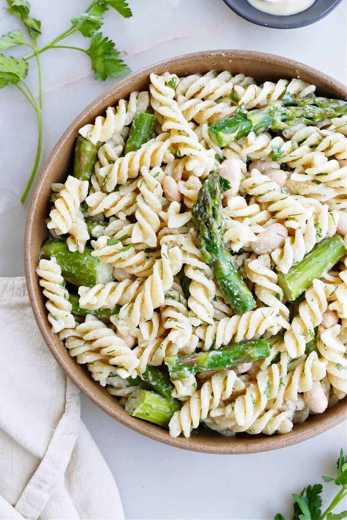 close-up image of pasta salad with asparagus and fresh herbs in a serving bowl