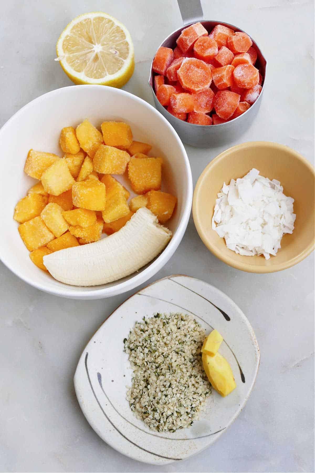 frozen carrots, mango, banana, hemp hearts, ginger, half a lemon, and coconut on a counter
