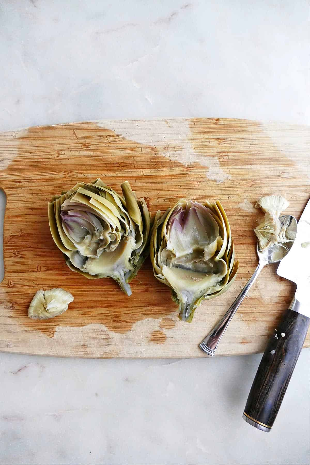 cooked artichokes cut in half on a cutting board with choke removed