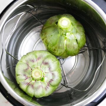 two artichokes upside down in an instant pot before cooking