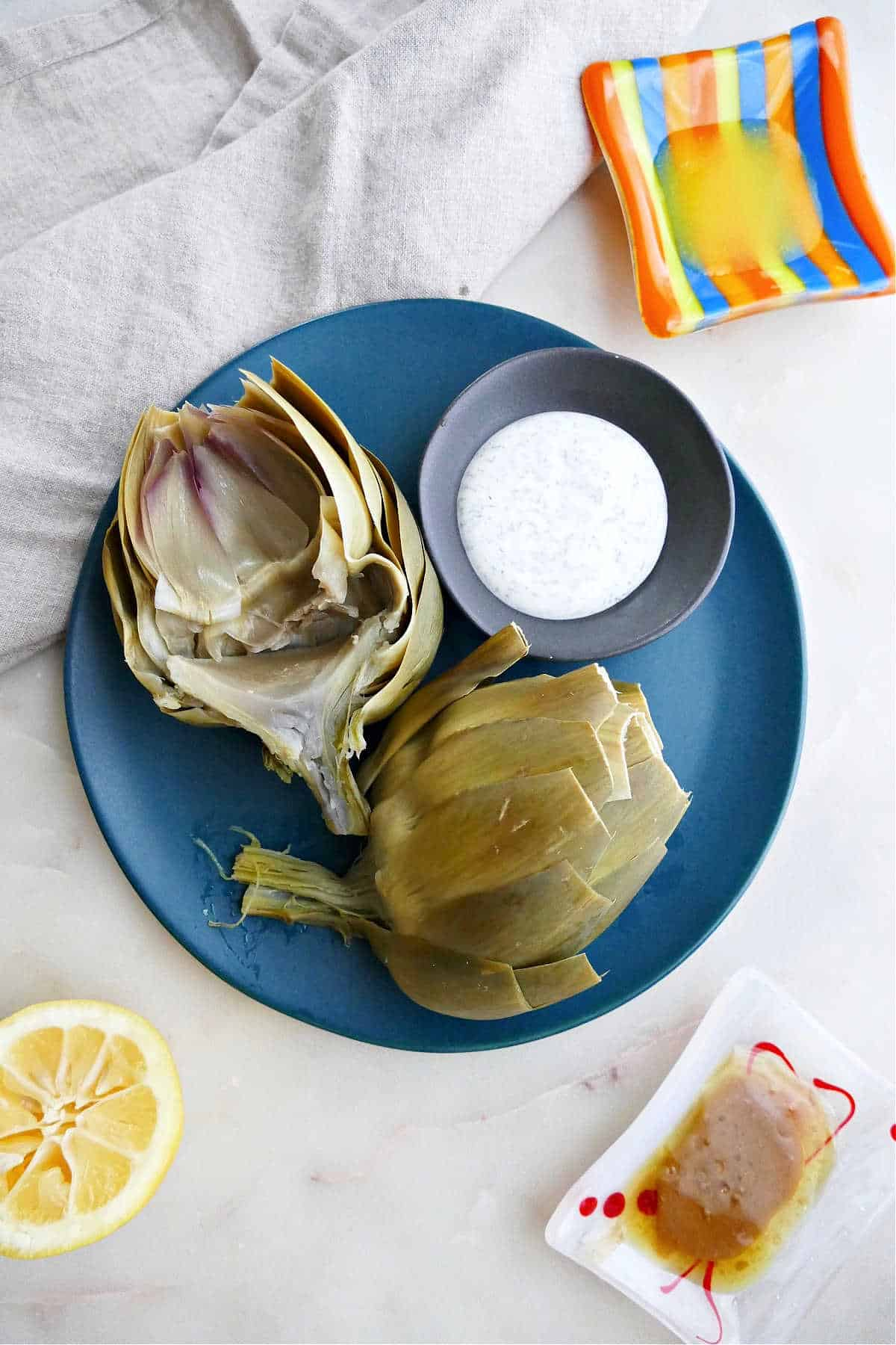 microwave artichoke sliced in half on a serving plate with dipping sauce