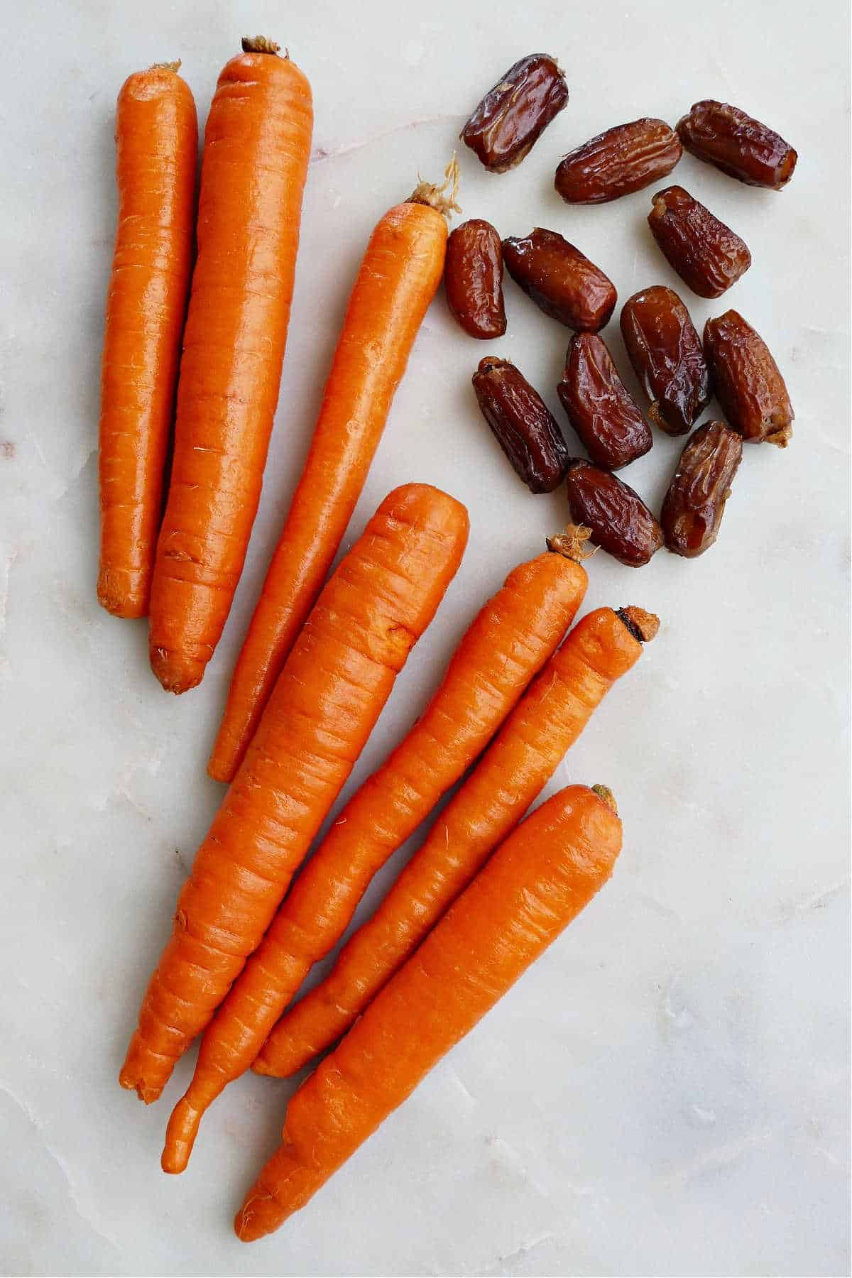 7 carrots next to 10 dates on a white counter