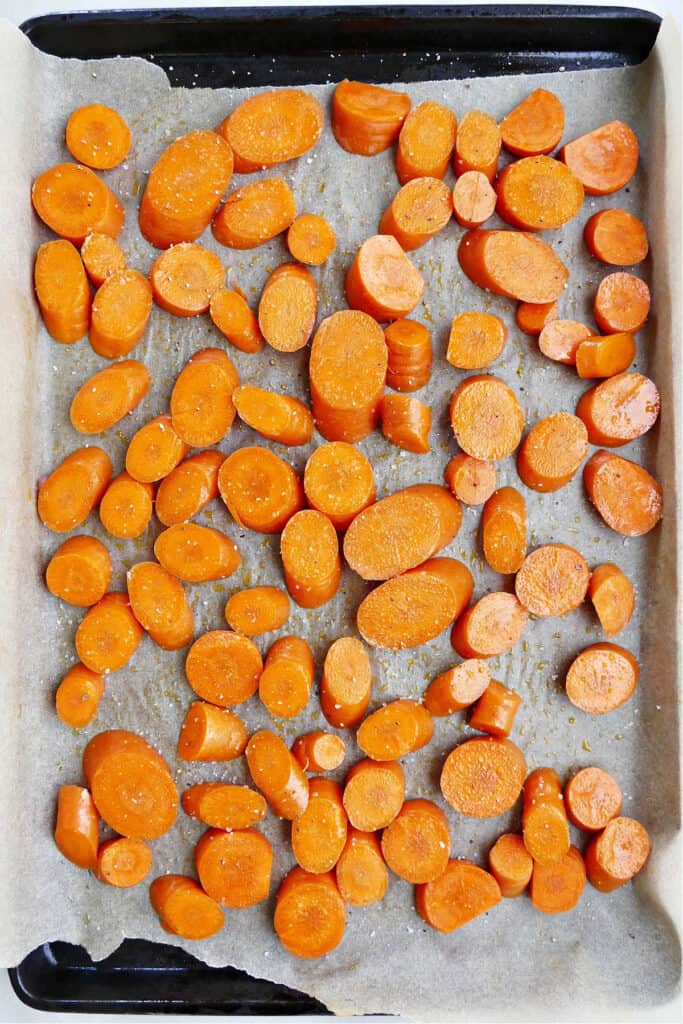 carrot coins cut on a diagonal spread out on a lined baking sheet