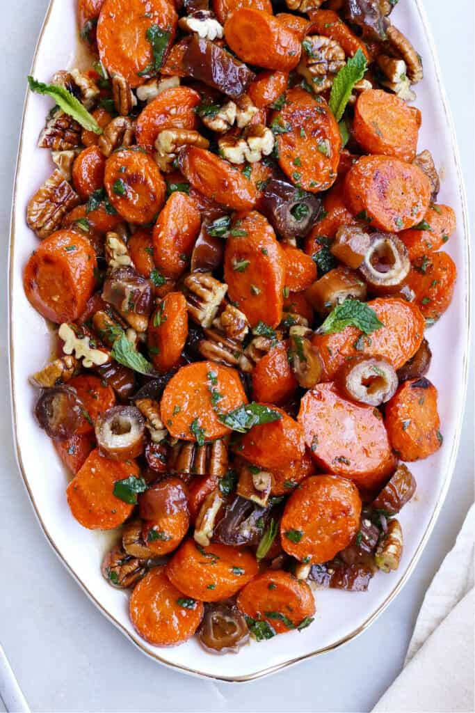 spiced carrots and dates on an oval serving dish on a counter