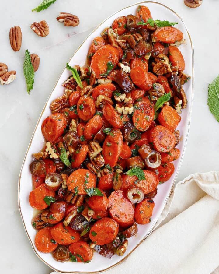 square image of spiced carrots and dates on an oval serving dish on a counter
