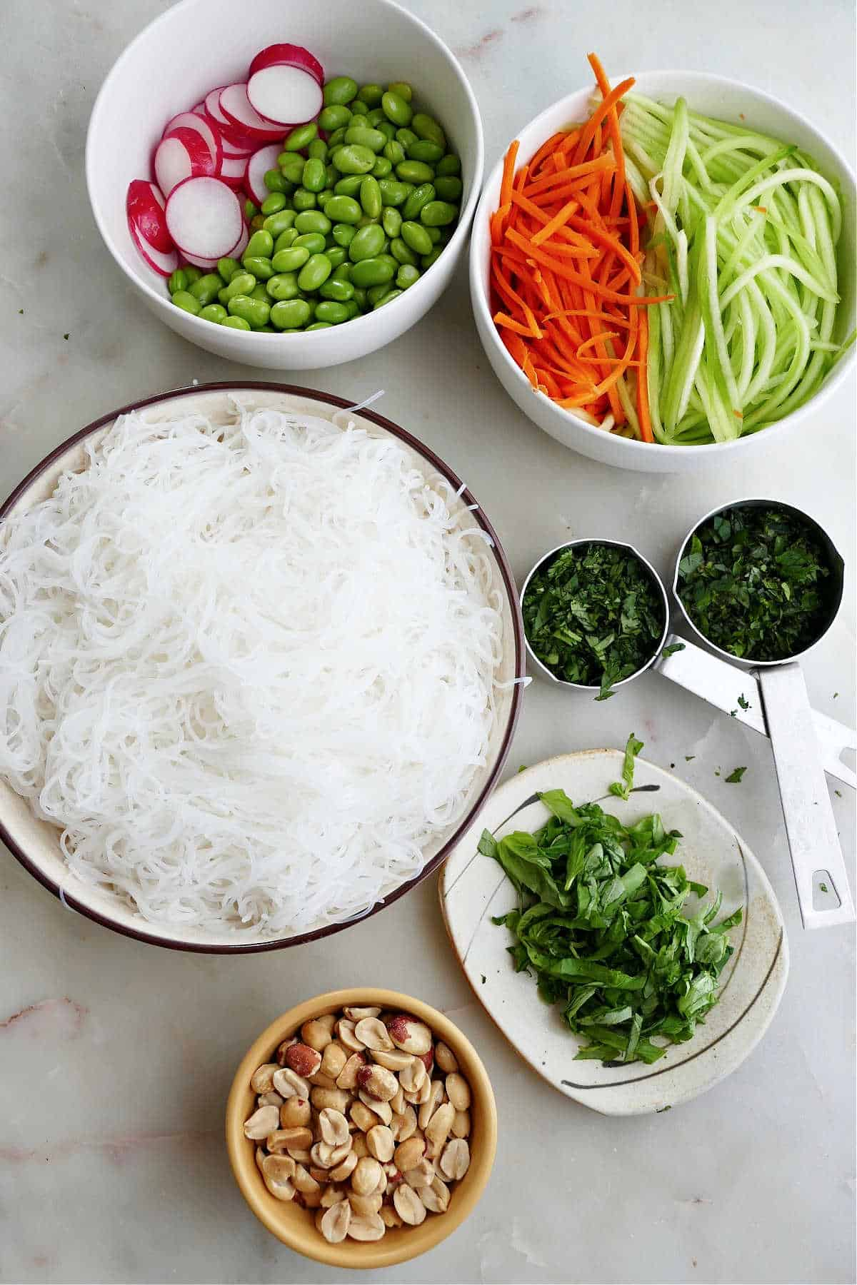 rice noodles, julienned vegetables, herbs, peanuts, and dressing ingredients on a counter