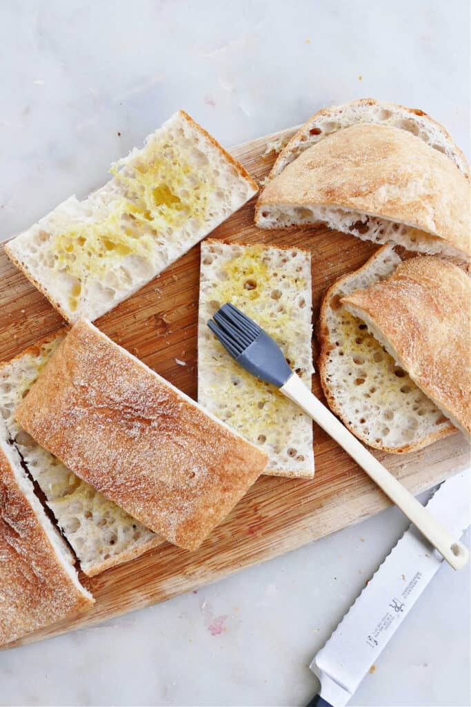 sliced ciabatta bread brushed with olive oil on a cutting board