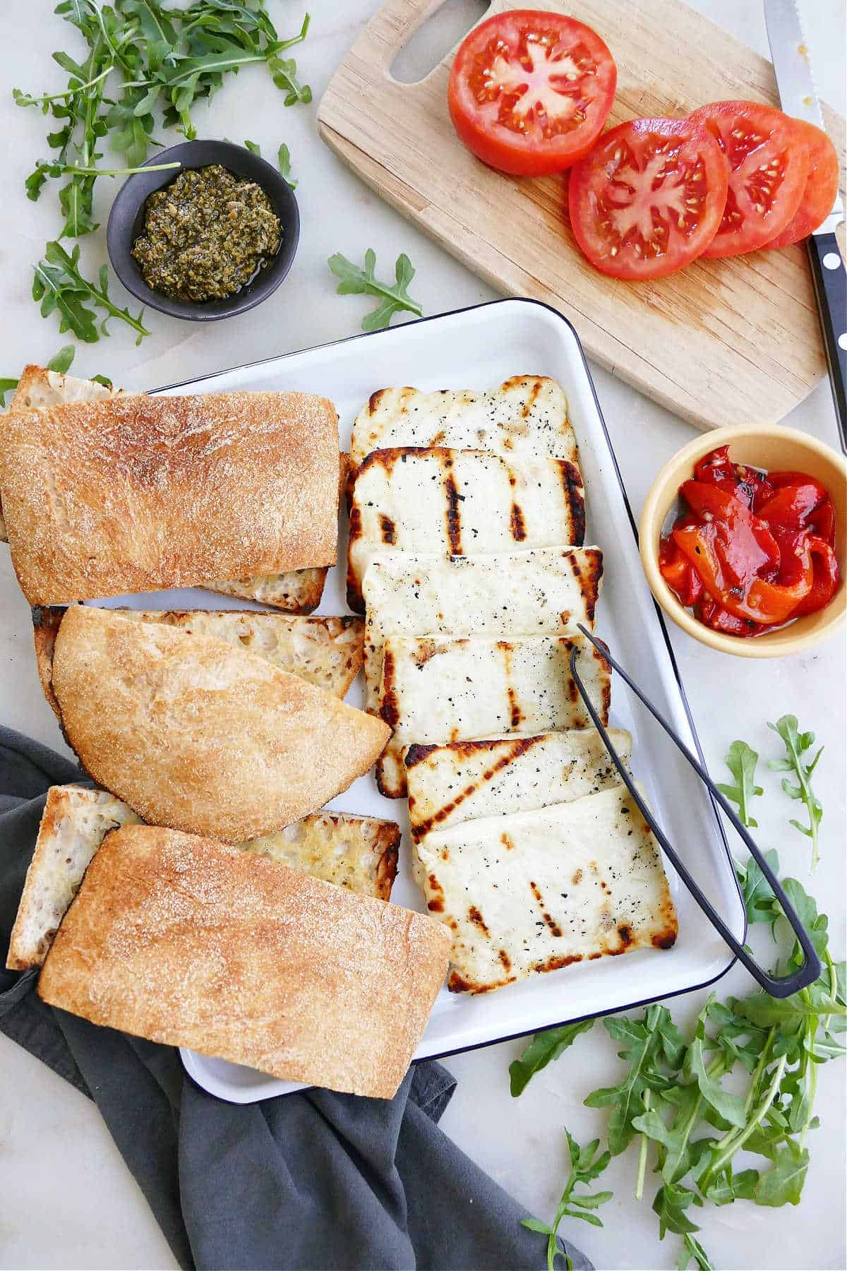 buffet spread for halloumi sandwiches with bread, tomatoes, arugula, peppers, and pesto