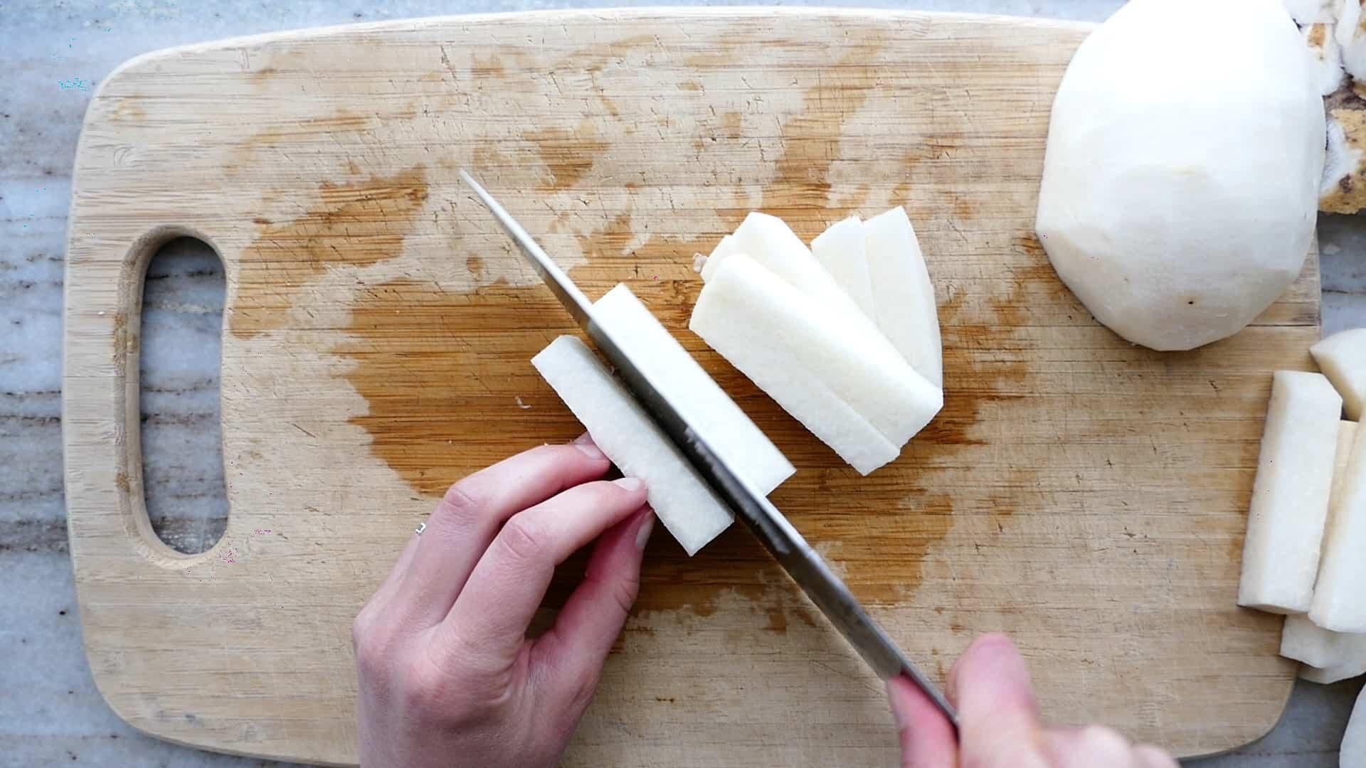 woman cutting jicama into matchsticks over a cutting board