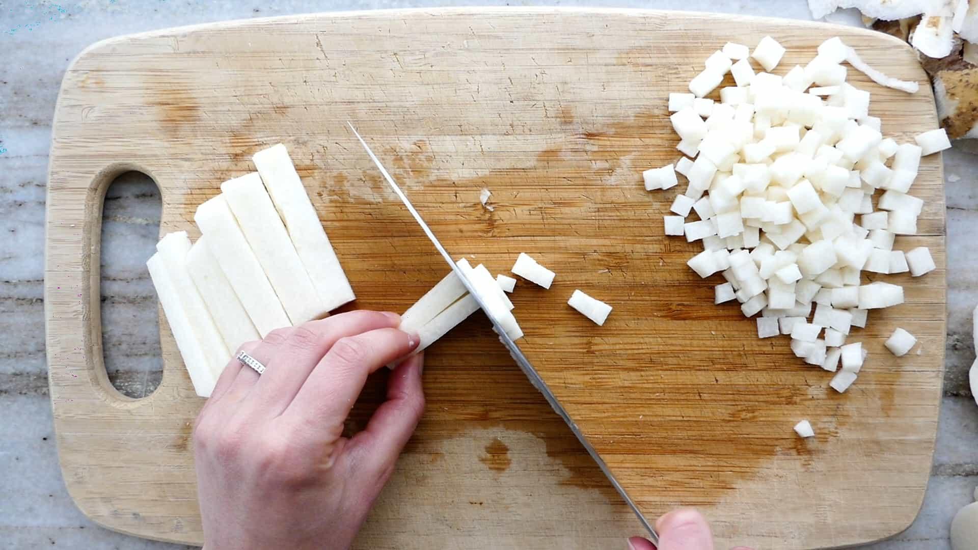 woman cutting jicama into cubes over a bamboo cutting board