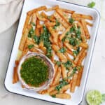 jicama fries drizzled with cilantro lime dressing on a serving tray on a counter
