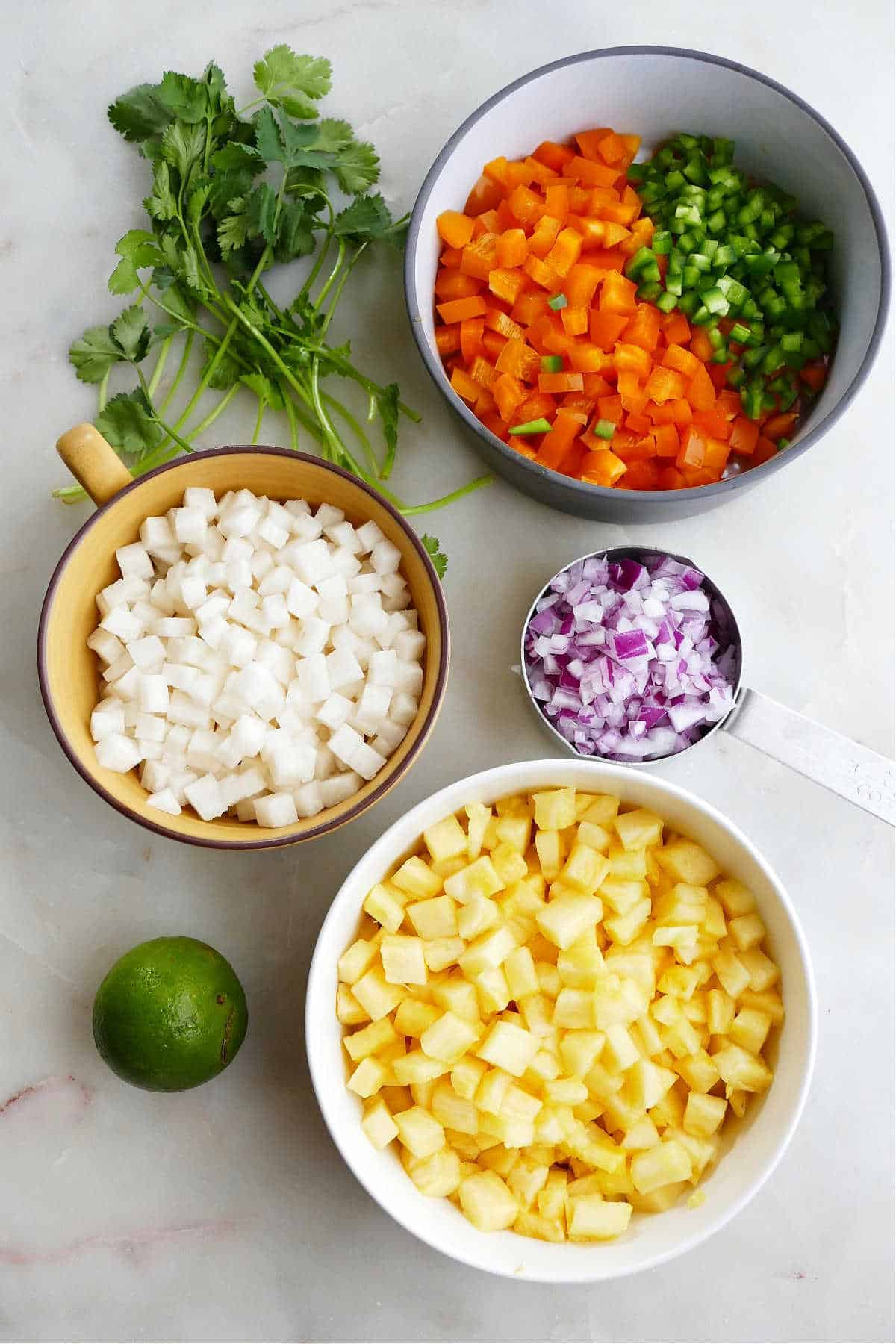 ingredients for pineapple jicama salsa spread out next to each other on a counter