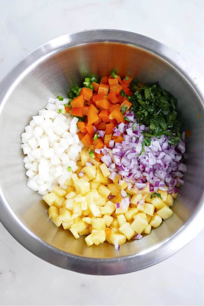 chopped jicama, pineapple, bell pepper, jalapeno, red onion, and cilantro in a bowl