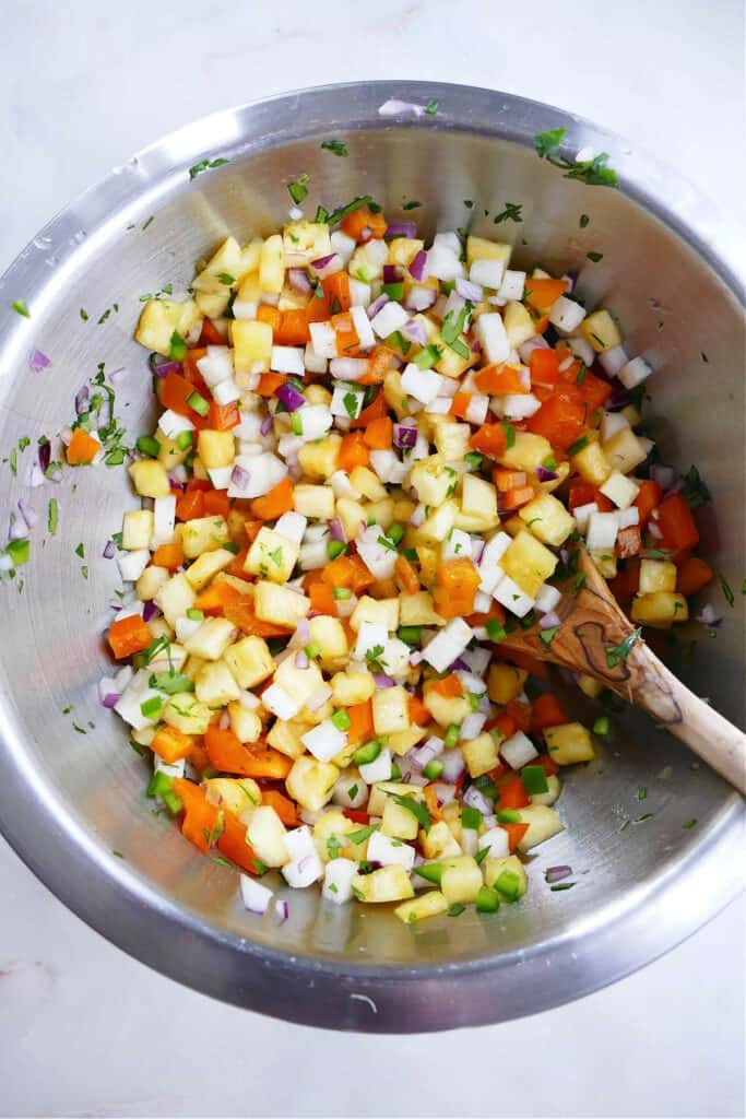 jicama salsa mixed together in a large bowl with a wooden spoon