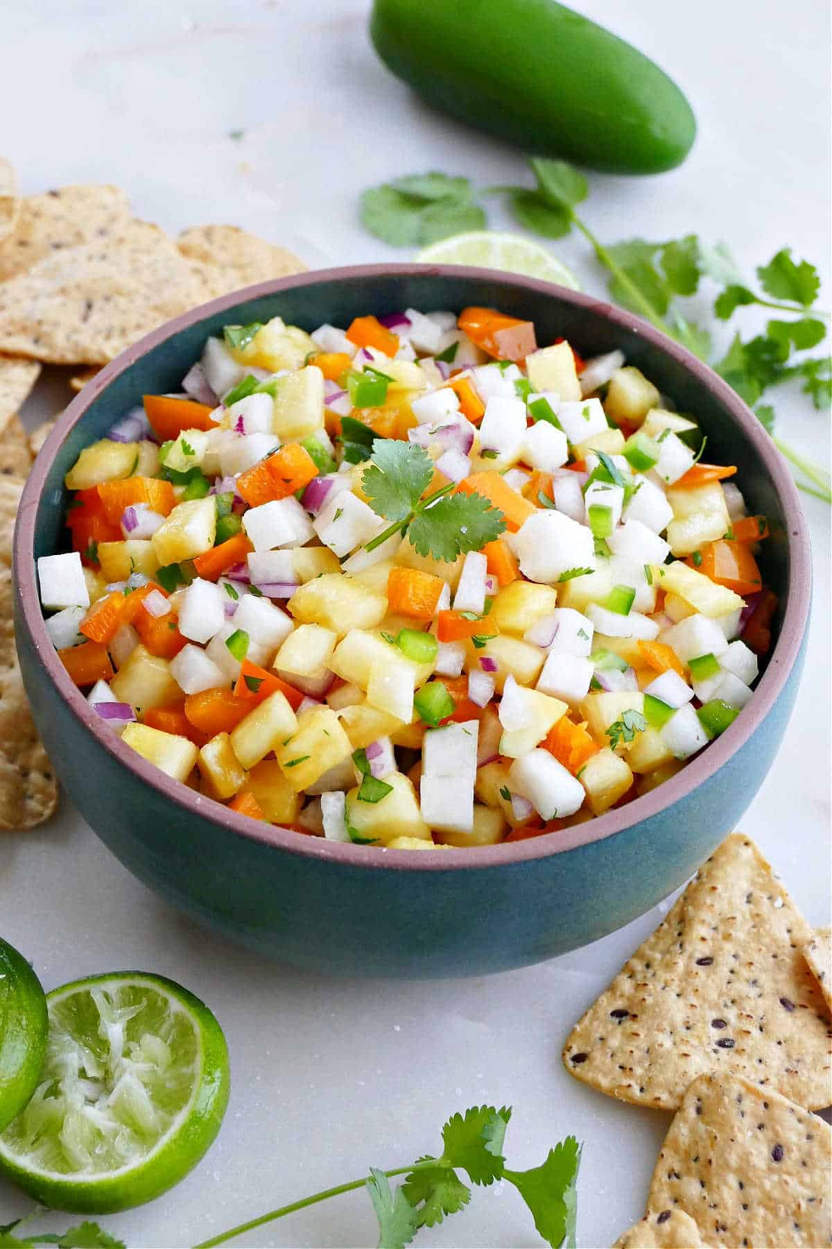 pineapple jicama salsa in a serving bowl surrounded by chips, lime, and cilantro