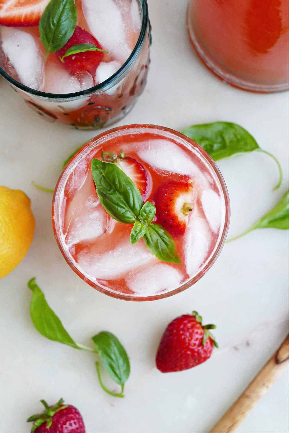 strawberry basil lemonade topped with basil leaves on a counter next to ingredients