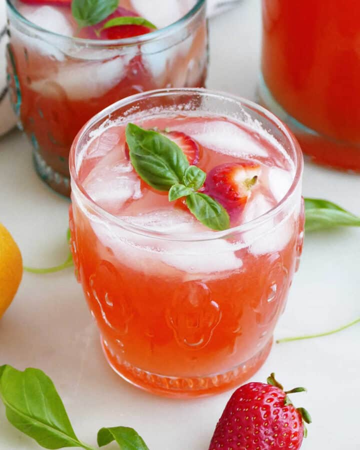 strawberry basil lemonade in front of another glass and pitcher on a counter