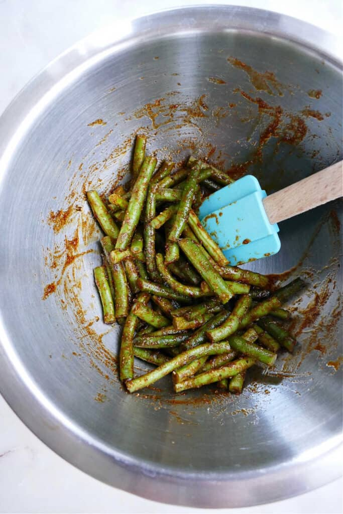 green beans being tossed in blackened seasoning with a rubber spatula in a bowl