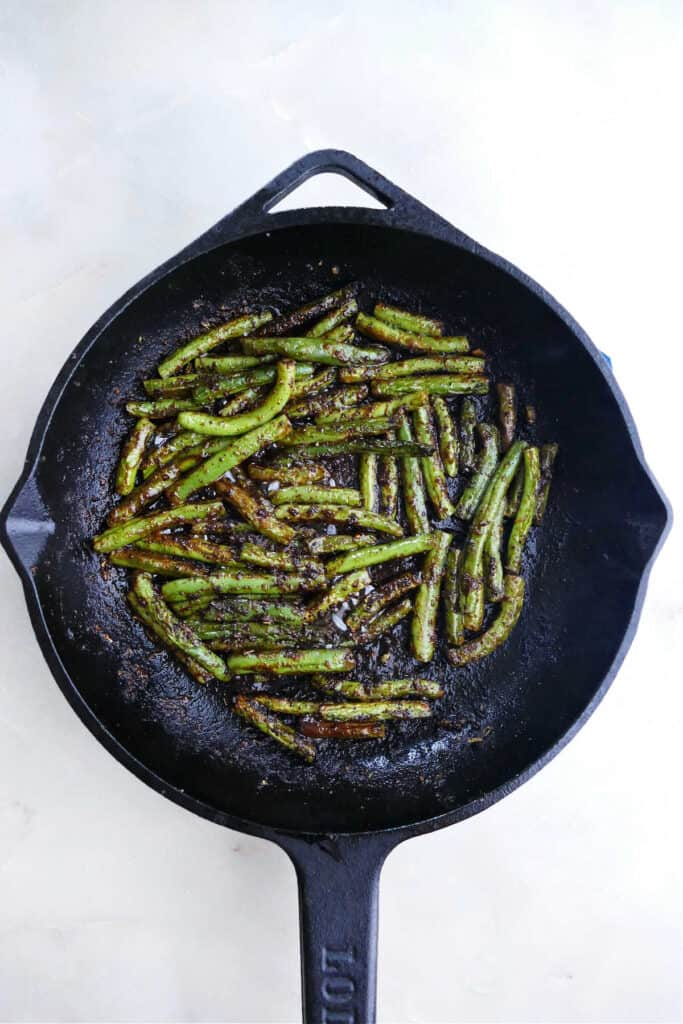 blackened green beans cooking in a cast iron skillet on a counter