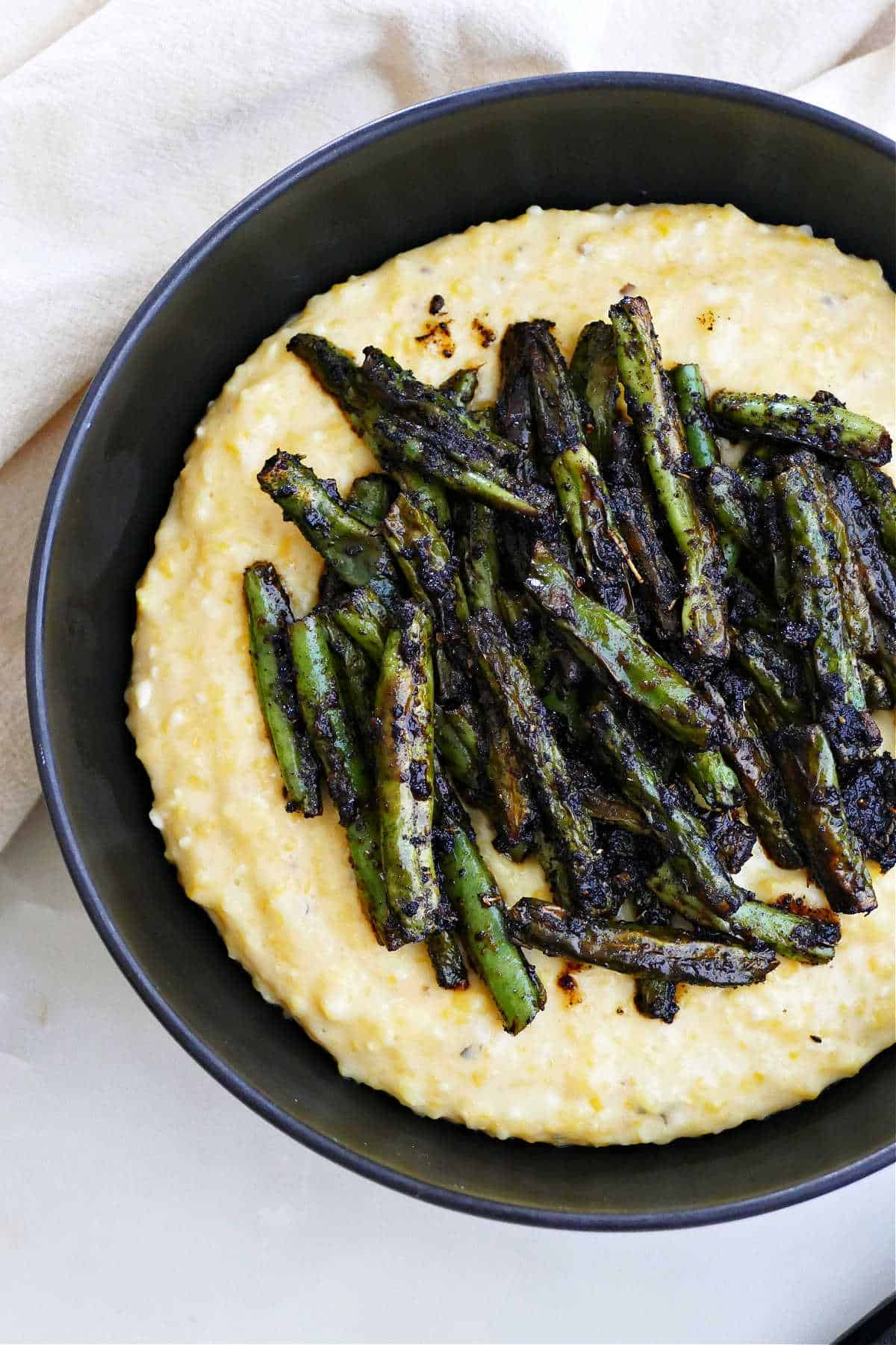 blackened green beans sitting on top of cheesy grits in a serving bowl