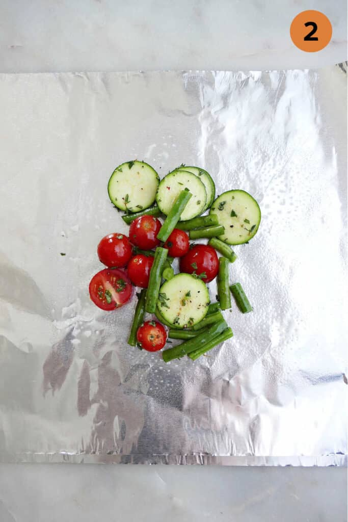 summer veggies on a piece of foil with the number two in a circle in the top right