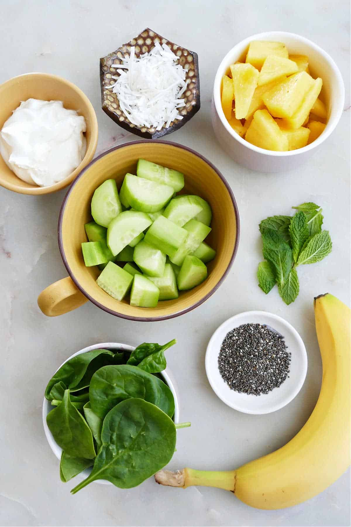 ingredients for a cucumber green smoothie spread out next to each other on a counter