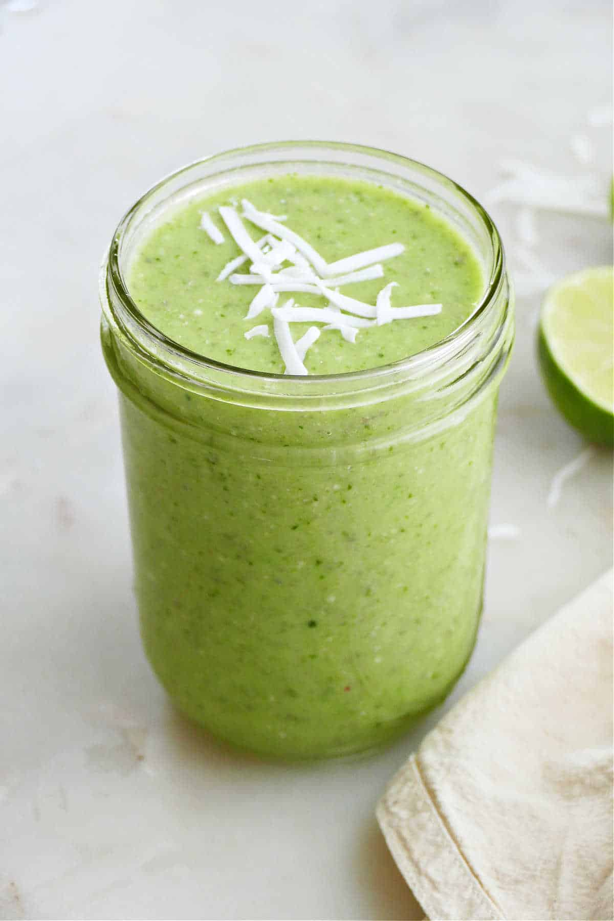 cucumber smoothie topped with shredded coconut flakes in a glass jar on a counter