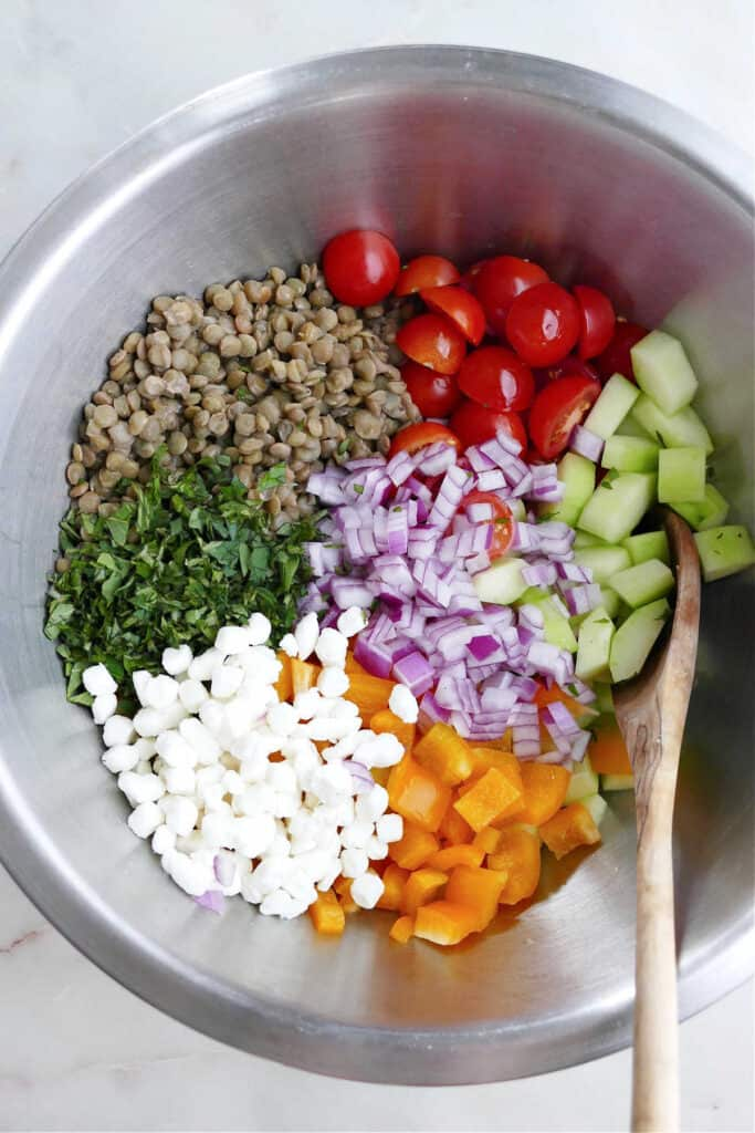 ingredients for Greek lentil salad in a large mixing bowl with a wooden spoon